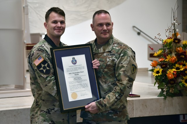 Sgt. Maj. David Clark, the U.S. Army Europe chief of religious affairs sergeant major, presents Staff. Sgt. Aaron Madasz, 2nd Cavalry Regiment, with the first Staff Sgt. Christopher Stout Medal signed by the chief of chaplains, Nov. 7, 2018.