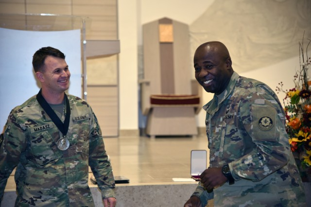 Maj. David Mvondo, 2nd Cavalry Regiment chaplain, congratulates Staff. Sgt. Aaron Madasz, 2CR religious support specialist, after he receives the first Staff Sgt. Christopher Stout Medal signed by the chief of chaplains, Nov. 7, 2018.