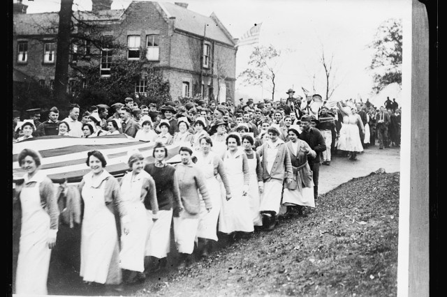 "Nurses from Brooklyn, N.Y. carry an American flag through the grounds of the American Base Hospital at Dartford, England, near London, on Nov. 11, 1918 after word of the signing of the Armistice ending the fighting broke. The ""Victory Parade"" covered a a three mile route, around the hospital grounds and through the German prison camp adjoining the American hospital."