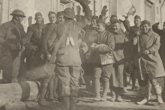 Soldiers of the New York National Guard's 27th Division celebrating the end of World War I following the Armistice on Nov. 11, 1918. According to Major General John O'Ryan, the commander of the division, this photo and others like it were staged in the days following the signing of the document that ended combat in the World War by U.S. Army Signal Corps photographers.
