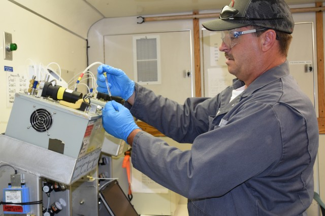 Lyle H. McClure, Blue Grass Chemical Activity monitoring system operator and mechanic, prepares to make a challenge injection to test the accuracy of MINICAM  agent readings on the Real-Time Analytical Platform.