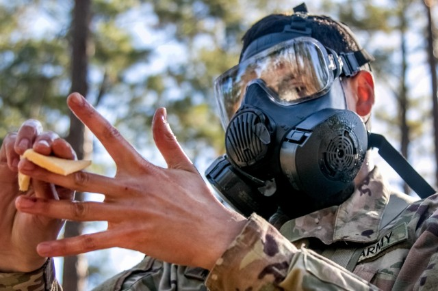 A combat medic assigned to the 82nd Airborne Division, Fort Bragg, N.C., wipes each finger with a decontamination wipe while competing for the Expert Field Medical Badge Nov.3, 2018, at Fort Bragg, N.C. The first week of testing introduces the candidates to all the tasks that they'll be expected to complete to earn the coveted badge. The EFMB was established to showcase and recognize medical Soldiers for their exceptional skill level and competence in the medical field. The testing consists of a written exam, land navigation, three separate combat testing lanes and concludes with a 12-mile ruck march. (U.S. Army photo by Sgt. Dustin Biven / 22nd Mobile Public Affairs Detachment)