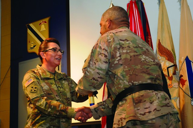 Brig. Gen. Douglas M. McBride Jr., the 55th Quartermaster General, passes the QM Corps Warrant Officer Regimental Charter to CW5 Maria G. Martinez during an assumption of responsibility ceremony Nov. 5 in Mullins Auditorium, Challen Hall. Martinez, the 15th Chief Warrant Officer of the QM Corps and a native of Mexico, is the first female to hold such a title in any of the U.S. Army Combined Arms Support Command's logistics branches. She replaced CW5 Jonathan O. Yerby, who is now the CASCOM CWO.