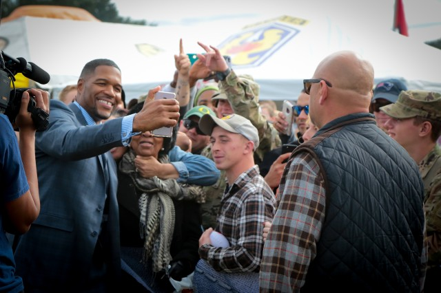 FORT BENNING, Ga. (Nov. 11, 2018) -- Professional football analyst and former defensive end Michael Strahan takes photos with fans at Fort Benning. Broadcasting live from Fort Benning, Georgia, the Maneuver Center of Excellence, Fox NFL Sunday celebrated Veterans Day and the centennial of Armistice Day with Soldiers and their Families at York Field in front of the Headquarters Building Nov. 11. The live NFL Fox Sports Sunday broadcast from Fort Benning is in honor of Veterans Day. (U.S. Army photo by Markeith Horace, Maneuver Center of Excellence, Fort Benning Public Affairs)