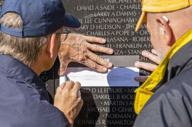 A visitor to the Vietnam Veterans Memorial traces the name of a U.S. service member killed during the Vietnam War in Washington, D.C., Nov. 11, 2018.
