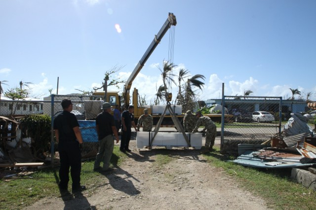 U.S. Army Reserve Soldiers with the 797th Engineer Company (Vertical), 9th Mission Support Command, and personnel with the Department of Fire and Emergency Services offload a FEMA tent as part of the Temporary Emergency Tent and Roofing Installation Support program implemented by the Commonwealth of the Northern Mariana Islands government and the FEMA, at a residency in Koblerville, Saipan, CNMI, Nov. 9, 2018. Service members from Joint Region Marianas and other units from within U.S. Indo-Pacific Command assigned to Task Force-West are providing Department of Defense support to the CNMI's civil and local officials as part of the FEMA-supported Super Typhoon Yutu recovery efforts.