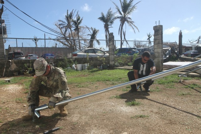 U.S. Army Reserve Spc. Richie Garcia, left, a Soldier with the 797th Engineer Company (Vertical), 9th Mission Support Command, currently assigned to Joint Task Group-Saipan, Task Force-West, assembles a FEMA tent with Department of Fire and Emergency Services personnel at a residential house lot in Koblerville, Saipan, Commonwealth of the Northern Mariana Islands, Nov. 9, 2018. Service members from Joint Region Marianas and other units from within U.S. Indo-Pacific Command assigned to Task Force-West are providing Department of Defense support to the CNMI's civil and local officials as part of the FEMA-supported Super Typhoon Yutu recovery efforts.