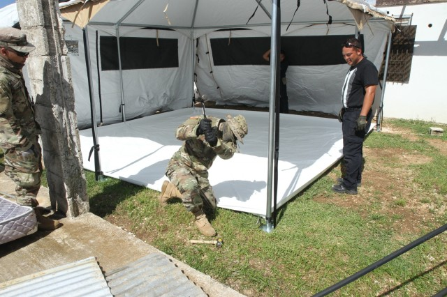 U.S. Army Spc. John Blas, a Soldier with the 797th Engineer Company (Vertical), 9th Mission Support Command, currently assigned to Joint Task Group-Saipan, Task Force-West, stakes a metal rod into the ground to secure a FEMA tent, which will be used as temporary shelter for Saipan residents impacted by Typhoon Yutu, Nov. 9, 2018. Service members from Joint Region Marianas and other units from within U.S. Indo-Pacific Command assigned to Task Force-West are providing Department of Defense support to the CNMI's civil and local officials as part of the FEMA-supported Super Typhoon Yutu recovery efforts.