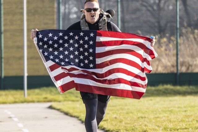 1Lt. Clayton Carroll holds the American flag as he crosses the finish line of the Veterans Day march at the International Peacekeeping ands Security Center, Ukraine, Nov. 11.