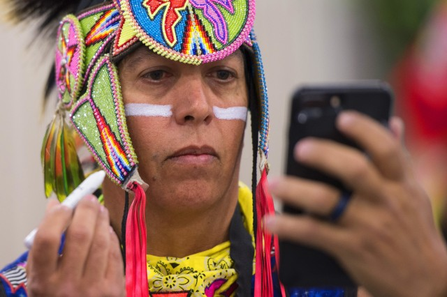 Army veteran Brian Hammill of the Ho-Chunk Nation applies face paint before grand entry at the 28th Annual Heard Museum World Championship Hoop Dance Contest at the Heard Museum in Phoenix, Arizona, Feb. 10, 2018. In the public Native American hoop dance performance, dancers can use up to 50 hoops to make formations that when combined convey a story.