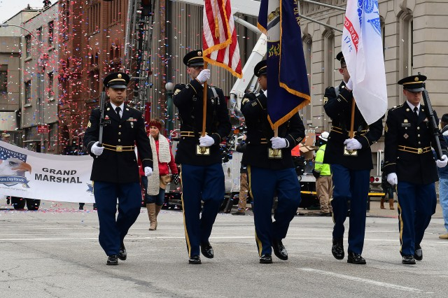 Color guard members from U.S. Army Recruiting Command march down a Louisville, Kentucky street to the applause and cheers of a lively crowd Nov. 9, 2018. Several hundred attended the Veterans Day parade in the city.