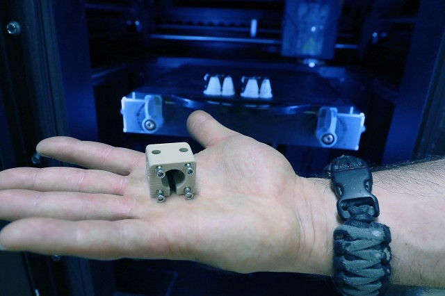"Parts known as ""3D printed 90-degree strain relief offset connectors"" are being produced in the background. The finished product is shown in hand. The connectors were designed/fabricated by REF engineers at Bagram Airfield, Afghanistan, to prevent cables from breaking when attached into a piece of equipment."