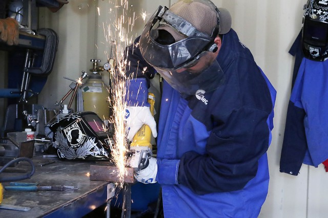 Ryan Muzii, a support engineer with U.S. Army Rapid Equipping Force's Expeditionary Laboratory at Bagram Airfield, Afghanistan, cuts metal for a project.