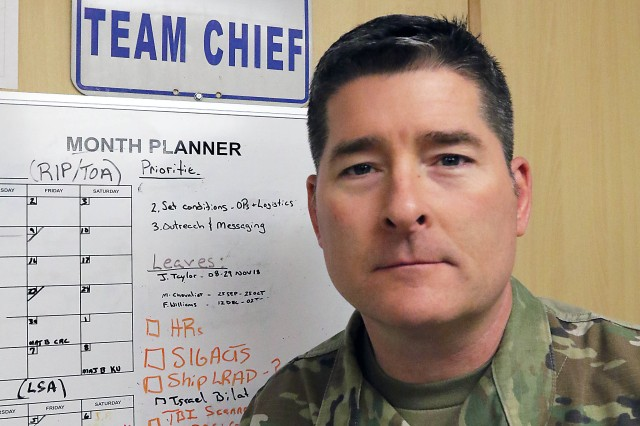 Lt. Col. Scott Cantlon, U.S. Army Rapid Equipping Forward Team chief, stands next to his organization's monthly planner. Cantlon has also spent time as the REF Forward Team chief in Iraq and Kuwait, and in Afghanistan for periods in 2016 and 2017.