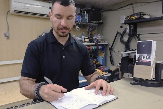 Ryan Muzii, a support engineer with U.S. Army Rapid Equipping Force's Expeditionary Laboratory at Bagram Airfield, Afghanistan, makes notes in a workbook. Muzii has nine years total working for the Ex Lab, whose headquarters is at Aberdeen Proving Ground, Md.
