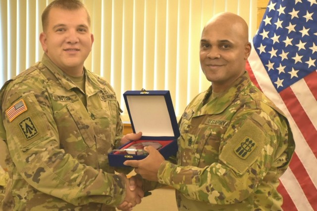 Staff Sgt. Joseph Butler from Charlie Battery, 2-1 Air Defense Artillery Battalion, presented guest speaker, Command Sgt. Maj. Randy B. Gray, 30th Air Defense Artillery Brigade command sergeant major, from Fort Sill, Oklahoma, with a thank you gift from the class.