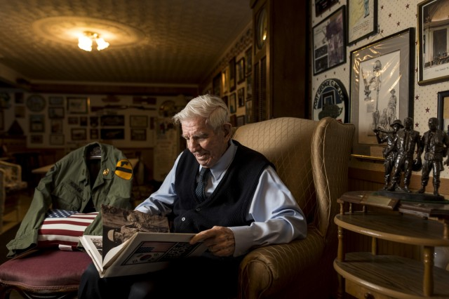 """Retired Sgt. Maj. Raymond Moran, affectionately known as the """"Old Soldier,"""" flips through a book on the Korean War during a portrait session in his home in Odenton, Md., while sharing stories about his military commitment to the U.S. Army and the U.S. Army Reserve during 65 years of service both as an enlisted Soldier and as a Department of the Army civilian. Moran served in Korea, Vietnam, Japan, Cambodia and during Desert Storm. He was instrumental in standing up the 220th Military Police Brigade, which has since become the 200th Military Police Command and is the largest military police organization in the U.S. Department of Defense."""