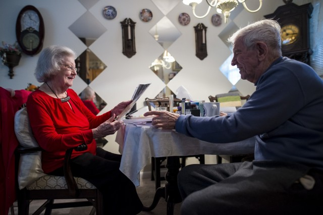 """Retired Sgt. Maj. Raymond Moran, affectionately known as the """"Old Soldier,"""" hands a picture to his wife at their breakfast table in Odenton, Md., Feb. 10, 2018. Raymond and Barbara have been married 65 years, the same number of years Moran spent in service to the U.S. Army and Army Reserve, combined, as an enlisted Soldier and as a Department of the Army civilian. Moran served in Korea, Vietnam, Japan, Cambodia and Desert Storm."""