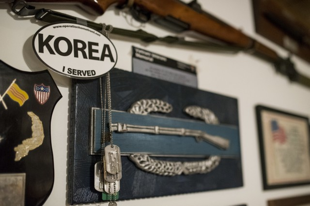 """An oversized Combat Infantry Badge hangs on the wall beneath a genuine M1 rifle in the basement of retired Sgt. Maj. Raymond Moran, affectionately known as the """"Old Soldier,"""" who lives in Odenton, Md. Moran earned the CIB in the Korean War. The rifle was a Veterans Day gift from his son. Moran spent 65 years both in the U.S. Army and U.S. Army Reserve as an enlisted Soldier and as a Department of the Army civilian, serving in Korea, Vietnam, Japan, Cambodia and during Desert Storm."""
