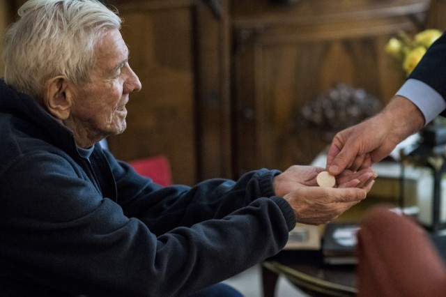 """Retired Sgt. Maj. Raymond Moran, affectionately known as the """"Old Soldier,"""" receives communion in his home along with his wife, administered by a deacon from their parish, St. Joseph Catholic Church in Odenton, Md., Feb. 22, 2018. The parish administers communion in their home because the Morans are not able to attend mass regularly due to their age and medical constraints. Raymond served in Korea, Vietnam, Japan, Cambodia and during Desert Storm."""