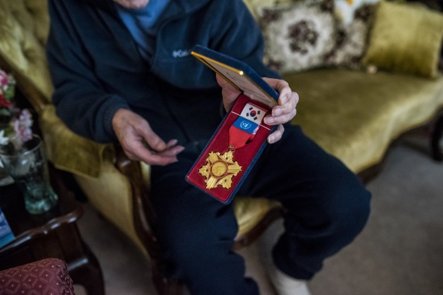 """Retired Sgt. Maj. Raymond Moran, affectionately known as the """"Old Soldier,"""" holds an honorary Korean War Memorial medal that he keeps on display in his home in Odenton, Maryland, Feb. 22, 2018. Moran devoted 65 years of service both as an enlisted Soldier and as a Department of the Army civilian in the U.S. Army and Army Reserve. He served in Korea, Vietnam, Japan, Cambodia and during Desert Storm."""