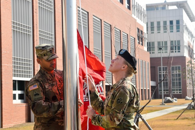 Col. Teresa Schlosser (right), U.S. Army Corps of Engineers (USACE), Far East District (FED) commander, and Master Sgt. David Montes, USACE FED district operation noncommissioned officer, prepare to raise the unit colors during an uncasing ceremony held at the district's headquarters, Camp Humphreys, South Korea, Nov. 14.