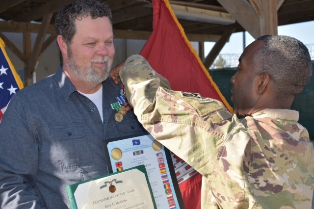 "Afghanistan District Commander, Colonel Jason Kelly presents Terry ""Hawk"" Hawkins with the NATO, Global War on Terrorism, and Commanders award for civilian service as the District bids him farewell and Tulsa District receives their team member back."