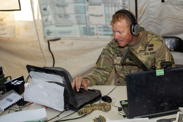 Maj. Shawn P. McNicol, Division Mission Command Node Officer-in-Charge for the 5th Squadron, 73rd Cavalry Regiment, 3rd Brigade Combat Team, Airborne Division from Fort Bragg, N.C., monitors chat with the Command Post Computing Environment (CPCE) during Network Integration Evaluation (NIE) 18.2, Nov. 1 to 12 at Camp McGregor, N.M.