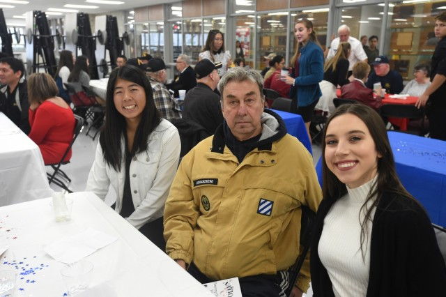 """Philip Schubitz, center, Vietnam-era veteran who served with the U.S. Army from 1968 to 1970, pauses for a photo with student Lauren Oda (left) and Jessica Pavliukovecas, during the Elk Grove High School Veterans Day ceremony, Nov. 9, 2018. U.S. Army Reserve Brig. Gen. Kris A. Belanger, Commanding General, 85th Support Command, was the keynote speaker for the event and attended with veterans from each of the service branches to include World War II veteran, Al Mampre, who served with the famed 101st Airborne Division's Easy Company, 506th Infantry Regiment. Mampre's unit story was featured on the mini-series """"Band of Brothers"""". Belanger also participated in a panel discussion with veterans sharing their stories and answering questions from the students about service. More than 2,000 students, faculty, veterans, and local community members attended the 5-hour event. (U.S. Army Reserve photo by Sgt. David Lietz)"""
