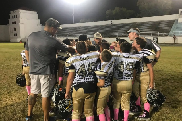In this courtesy photo, Sgt. 1st Class Jesse Goad, left, a platoon sergeant for B Troop, 1st Squadron, 16th Cavalry Regiment, coaches 9- and 10-year-olds on playing football at Doughboy Stadium at Fort Benning, Georgia. (Photo courtesy of Fort Benning Bengals)