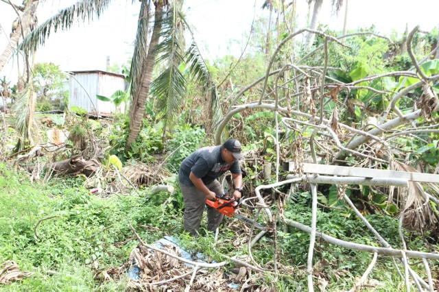 U.S. Army Reserve Staff Sgt. Cristin Duenas Jr., a Soldier with 302nd Quartermaster Company, 9th Mission Support Command, currently assigned to Joint Task Force Group-Saipan in support of Super Typhoon Yutu recovery efforts, uses a chainsaw to clear a fallen tree at a fellow Soldier's home while off-duty, Nov. 13, 2018, Saipan, Commonwealth of the Northern Mariana Islands. Service members from Joint Region Marianas and other units from within U.S. Indo-Pacific Command assigned to Task Force-West are providing Department of Defense support to the CNMI's civil and local officials as part of the FEMA-supported Typhoon Yutu recovery efforts