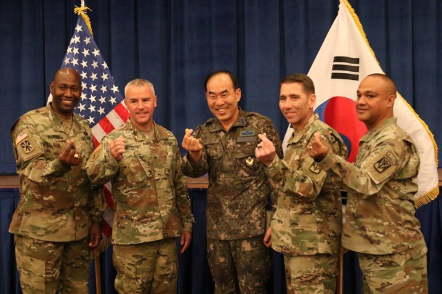 94th Army Air and Missile Defense Command senior enlisted advisor and commander, Command Sgt. Maj. Eric McCray and Brig. Gen Michael Morrissey; Brigadier Gen. Park Chan Sik, Republic of Korea 2nd Air Defense Artillery Brigade Commander and 35th ADA Brigade command team, Col. Richard Wright and Command Sgt. Maj. Wilfredo Suarez, demonstrate an endearing South Korean gesture of fondness at the Missile Defender of the Year Banquet Nov. 16, at Osan Air Base.