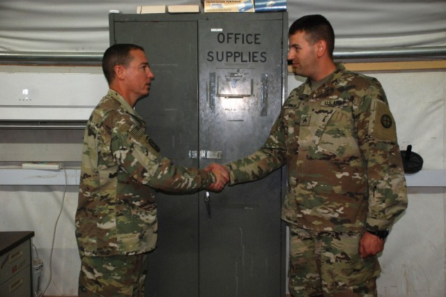 U.S. Army National Guard Col. Charles Hausman, commander of the 35th Combat Aviation Brigade, left, presents a leadership coin for excellence to Sgt. James Aiman, a senior information system specialist assigned to Headquarters and Support Company, 935th Aviation Support Battalion, at Camp Buehring, Kuwait, Oct. 6, 2018.  Hausman was visiting Soldiers of the 935th ASB during their deployment in support of Operations Inherent Resolve and Spartan Shield.  (U.S. Army National Guard photo by Sgt. Billie Thompson)