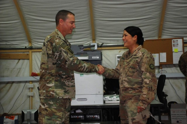 U.S. Army National Guard Col. Charles Hausman, commander of the 35th Combat Aviation Brigade, left, presents a leadership coin for excellence to Spc. Valencia Marlowe, a material store handling specialist assigned to A. Company, 935th Aviation Support Battalion, at Camp Buehring, Kuwait, Oct. 6, 2018.  Hausman was visiting Soldiers of the 935th ASB during their deployment in support of Operations Inherent Resolve and Spartan Shield.  (U.S. Army National Guard photo by Sgt. Billie Thompson)