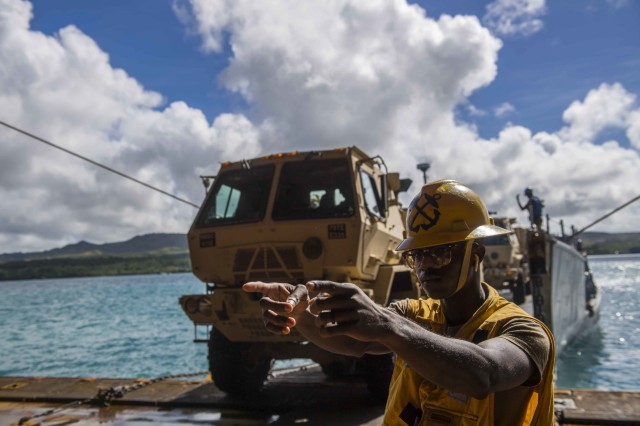 Boatswain's Mate 3rd Class Nayyaamunhotep Stubbs signals a 10-ton dump truck from the 9th Mission Support Command, 411th Engineer Brigade, Guam Army National Guard to drive inside the well deck of the amphibious dock landing ship USS Ashland (LSD 48) to transfer the equipment to the island of Saipan for Defense Support to Civil Authorities (DSCA) efforts. Sailors and Marines from Ashland, assigned to Commander, Amphibious Squadron 11, are providing Department of Defense support to the Commonwealth of the Northern Mariana Islands' civil and local officials as part of the FEMA-supported Typhoon Yutu recovery efforts.