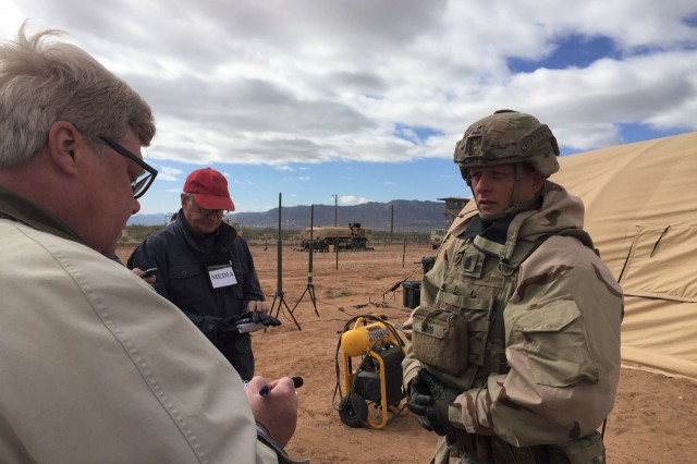 "Command Sgt. Maj. Robert Cobb, senior enlisted advisor for 1st Armored Division and Fort Bliss, conducts an interview with ""Tom Gauer"", a role-playing reporter, on the status of operations within the Warfighter exercise scenario Nov. 12 outside the division's main command post. Senior leaders were provided media training to make sure they understand the importance of engaging with the media to inform the American public about the U.S. Army's operations. The purpose of Warfighter 19-2 was to train the 1st Armored Division in a demanding exercise that tests America's Tank Division, and its Soldiers on all warfighting functions while simultaneously conducting operations in a simulated, complex combat environment."