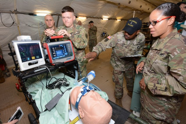 Chief Warrant Officer 2 Goldie Cooper (center) assigned to the Army Medical Department Board checks the status of the intrathoracic pressure regulation therapy device at a Deployable Medical Systems Equipment of Training Complex at Camp Bullis, Texas.