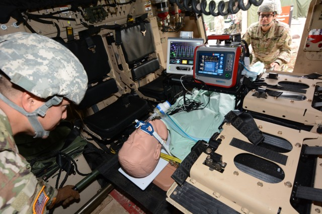 Soldiers testing the intrathoracic pressure regulation therapy device load it onto an MRAP.