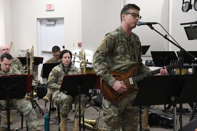 """Sgt. William Wallace gets to rock out on guitar and vocals on U2's """"Christmas (Baby Please Come Home)"""" during a 10th Mountain Division Band rehearsal Nov. 15 in preparation for the holiday concert series in December. (Photo by Mike Strasser, Fort Drum Garrison Public Affairs)"""