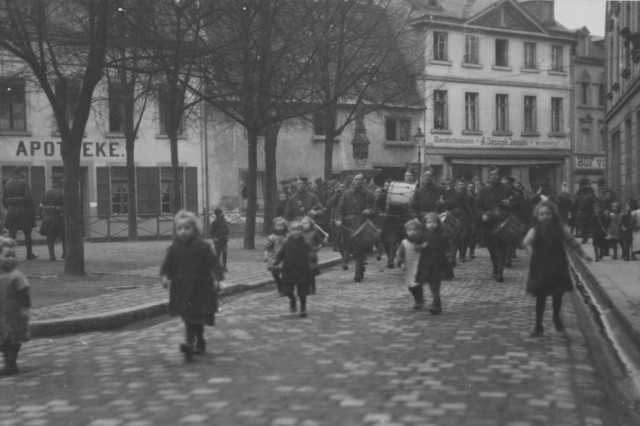 U.S. Army National Guard Soldiers assigned to the 165th Infantry Regimental Band approach a square in a town along the Rhine River in Germany during their march into Germany for occupation duties in December 1918. The 165th Infantry was renamed from the New York National Guard 69th Infantry Regiment, based in New York City and comprised mainly of Soldiers from Irish lineage. The 42nd Division, known as the Rainbow Division for its inclusion of various National Guard units from across the United States, served as an occupation force following the armistice that ended World War I. The division served in Germany until April 1, 1919 when it embarked for its journey home.