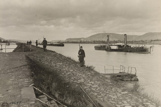 "Army Soldiers of the 42nd ""Rainbow"" Division pace up and down the waterfront performing sentry duty near Nieder Breisig, Germany, December 19, 1918. The unit was known as the Rainbow Division for its inclusion of various National Guard units from across the United States, served as an occupation force following the armistice that ended World War I. The division served in Germany until April 1, 1919 when it embarked for its journey home."