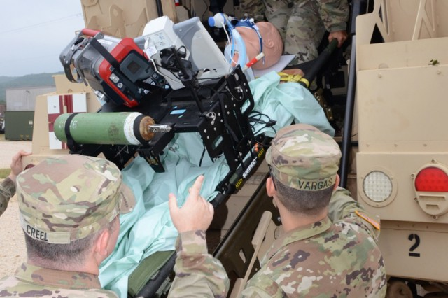 Soldiers testing the intrathoracic pressure regulation therapy (IPRT) device load it onto an MRAP.