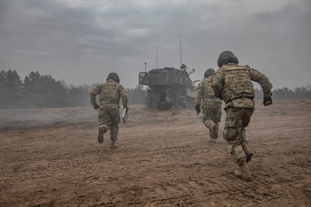 U.S. Army M109 Paladin artillery crew-members race into their gun after pulling the initial round from a 50ft. lanyard during NATO joint training exercise, Anakonda-18 (AN-18), at Bemowo Piskie Training Area, Poland, Nov. 14. AN-18 is a 10-day log training exercise designed to strengthen the interoperability between participating nations by developing strategies in defensive operations and execution to better prepare against any form of threat against NATO allies.