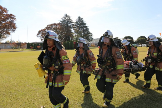 Tsuyoshi Nakayama, left, a Sagamihara City firefighter, guides his team as the practice rescuing a simulated injured victim during a UH-60 helicopter incident bilateral training exercise co-hosted by U.S Army Garrison Japan and U.S. Army Aviation Battalion Japan on Nov. 16, 2018, on Sagami General Depot, Japan. The Garrison and aviation battalion co-hosted the event to improve their emergency response capabilities and bilateral work with off-post first-responders from Sagamihara City.