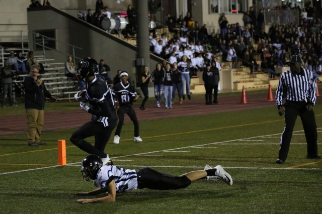 Zama wide receiver Caen Hammond scores a touchdown, leaving an Osan Cougar defender sprawled in the end zone during the Far East Division II Championship Football Game on Camp Zama, Japan, Nov. 10, 2018.