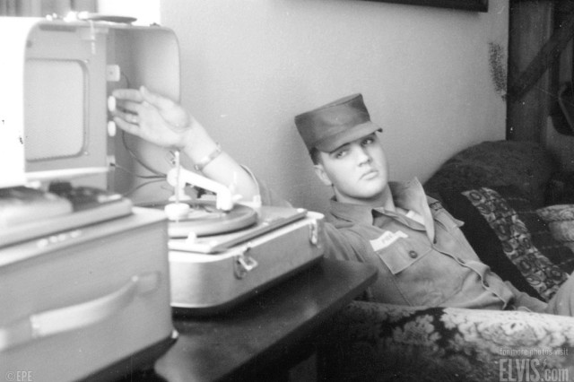 Elvis listens to a 45rpm record on a portable player, possibly one of his own songs.