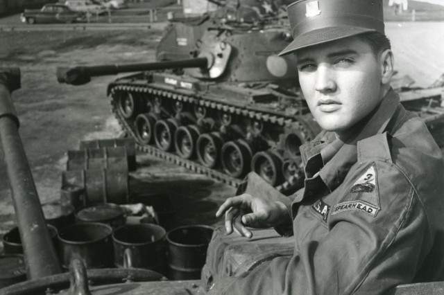 Elvis poses by one of his division's tanks.