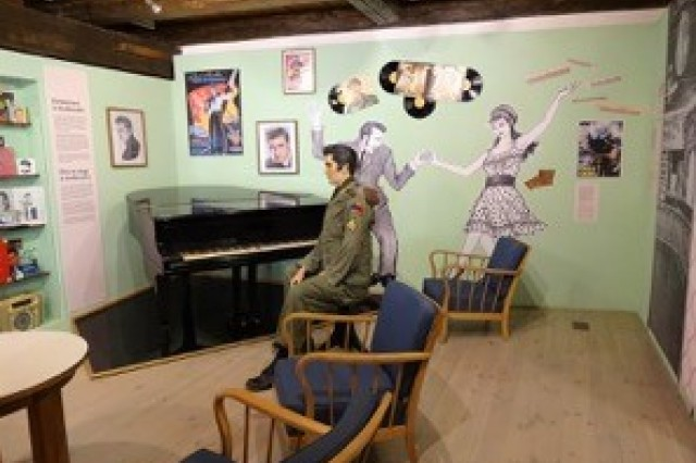 """One of the museum exhibits is a reproduction of the """"Micky Club,"""" where Elvis put on an impromptu concert for an audience of German and American friends and family. The piano and the stool the mannequin sits upon were both used by the king for that concert."""