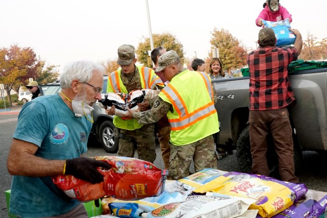 Spc. Mark Maynard and Pfc. Christian P. Reinke, military police officers with the 870th Military Police Company, helps local community members unload donations at a temporary animal shelter at the municipal airport in Chico, California, Nov. 18, 2018. In response to the Camp Fire, the airport has been converted to a temporary animal shelter, caring for displaced animals and providing donations to pet owners in need.
