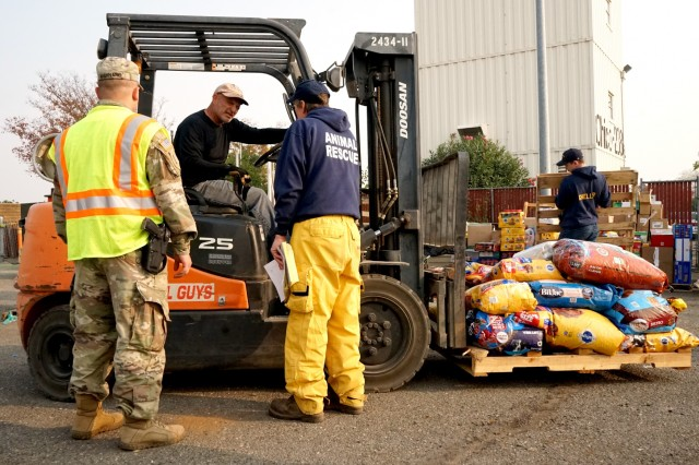 Spc. Mark Maynard, a military police officer with the 870th Military Police Company, and Norm Rosene, Public Information Officer for the North Valley Animal Rescue Group, direct a volunteer moving donations at the municipal airport in Chico, California, Nov. 18, 2018. In response to the Camp Fire, the airport has been converted to a temporary animal shelter, caring for displaced animals and providing donations to pet owners in need.